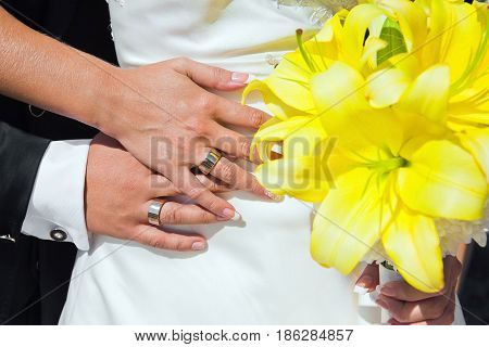 Bride and groom hands with wedding rings and bouquet