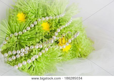 White necklace of pearls and bouquet of green chrysanthemums on a white veil