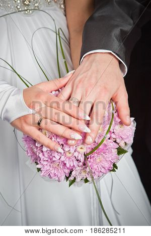 Hands of groom and bride lie on wedding bouquet background of pink chrysanthemums