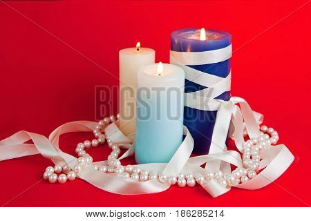 Three burning candles with a tape and a pearl beads on the red background