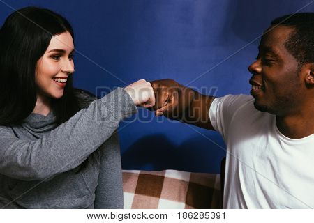 Young couple of black man and white woman on couch, closeup. Fist bump, togetherness, smile, joy, happiness, international friendship concept.