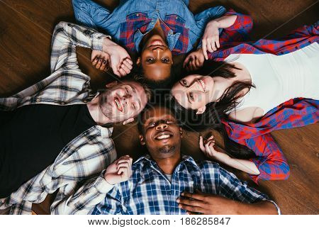 Happy group of four young black and white friends, pastime together. International friendship, fun, happiness and joy, world unity and race equality concept.