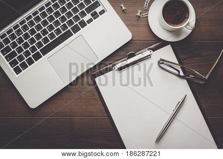 top view of an office table. brown wooden office desk with cup of coffee, notepad and laptop computer. working office space. office objects on the table. office working atmosphere