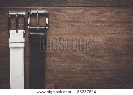 brown and white men's leather belts. belts on wooden background. men's belts on the brown table. top view of men's belts. brown and white men's belts background with copy space.