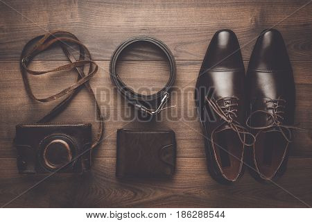 brown men's leather accessories shoes, purse, belt, and film camera. leather accessories on brown table. top view of leather accessories. leather accessories on wooden background.