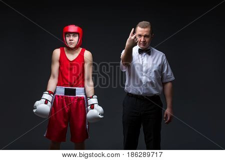Referee giving penalty point to young boxing sportsman before fight. Studio shot on black background. Copy space.