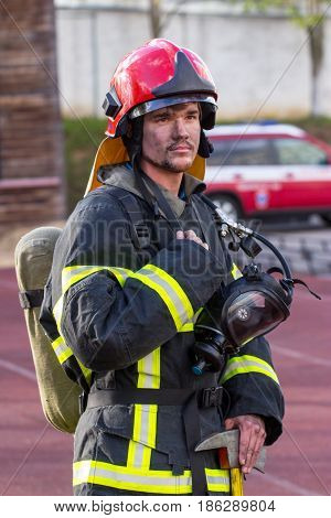 Portrait of heroic fireman with an axe outdoors.
