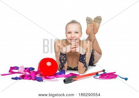beautiful blond teen age gymnast girl with ball, tape, hula hoop and maces sitting on floor. Studio shot isolated on white background. Copy space.