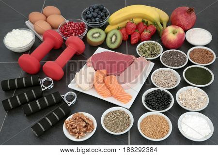 Large health food collection for body builders with dumbbell weights and hand grippers on slate background.