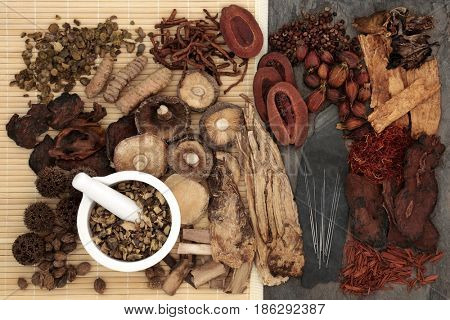 Traditional chinese herbal medicine selection with acupuncture needles and mortar and pestle forming a background.