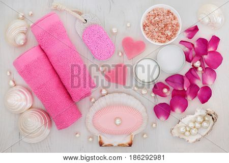 Bathroom and spa beauty treatment accessories with rose petals, himalayan salt, pumice, soaps, pink face towels, shells and pearls on distressed wood background.