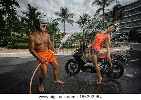 Portrait of couple having fun with garden hose splashing summer rain on scooter