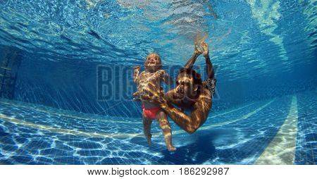 Funny photo of happy active family young father with active baby diving in swimming pool with fun jump deep down underwater.