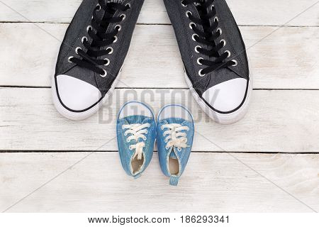Daddy's boots and baby's shoes fathers day concept. flat lay