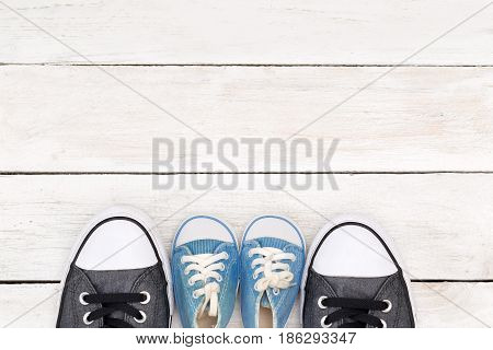 Daddy's boots and baby's sneakers on white wooden background father's day concept.