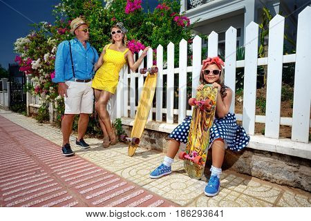 Vintage family walking  and  their daughter  having fun with skateboard in the suburb street