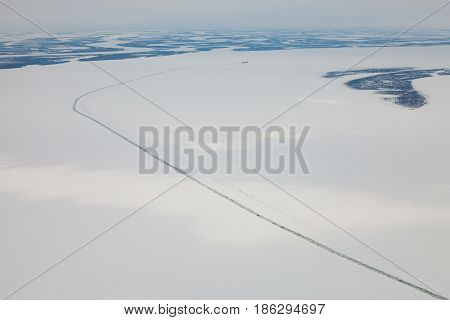 Icebreaker on the frozen Yenisei river during winter. Aerial view.