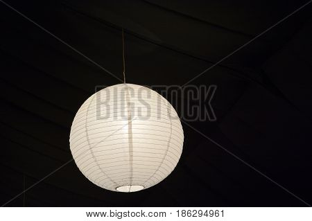 White paper lantern lamp hang from a ceiling. Asian background