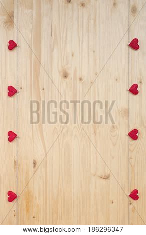 Eight hearts with clothes pegs on a cord on wood