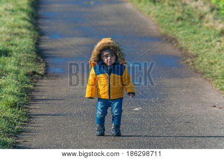 Little boy is laughing and walking on a country road.