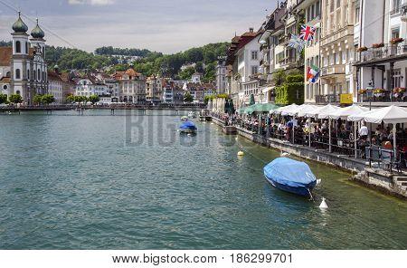 LUCERNE, SWITZERLAND - JUNE 12, 2013: People rest in sidewalk cafes, Switzerland, Lucerne, Reuss river,