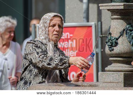 LUCERNE, SWITZERLAND - JUNE 12, 2013: Elderly muslim woman fill bottle drink water from drinking fountain.  Lucerne, Switzerland. bottle