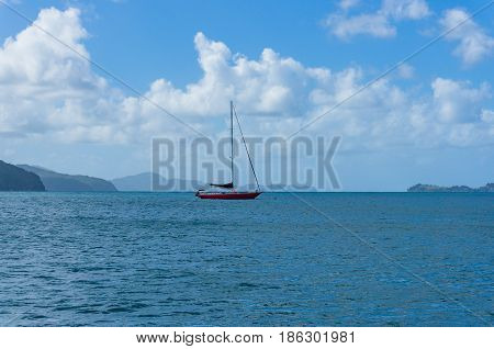 Red sail boat yacht on calm sea with coral reef islands in the distance. Whitsunday Australia