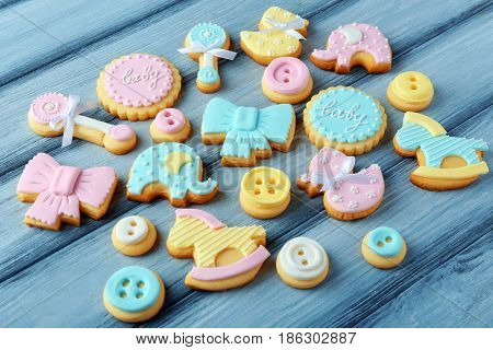 Baby cookies decorated with glaze on wooden background