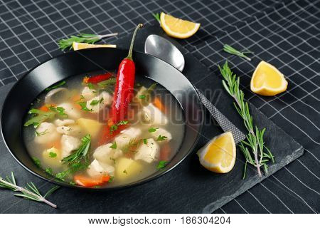 Plate with chicken soup and chili pepper on table