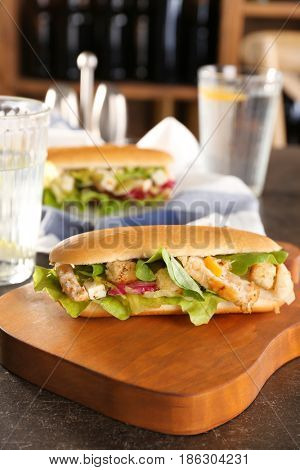 Wooden board with chicken salad in hot dog bun on table