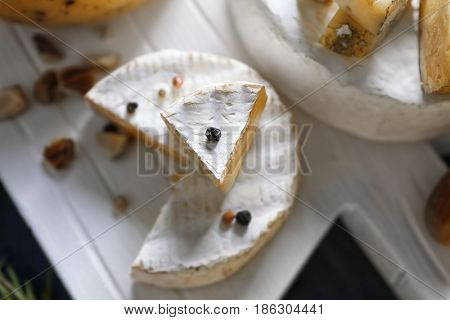 Camembert cheese on white wooden board