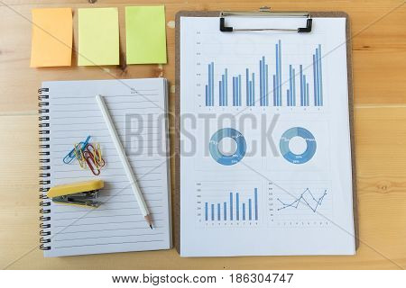 Marketing Graph And Chart Report With Pencil, Notebook, Sticky Note, Stapler, Paper Clip On Office D
