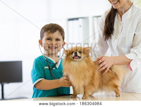 Child boy at the veterinary doctor with his dog