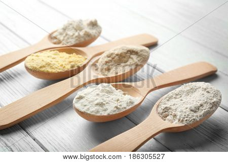 Spoons with different types of flour on light wooden background, closeup