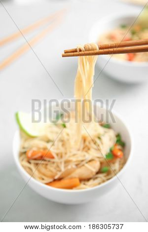 Wooden chopsticks with rice noodle on blurred background