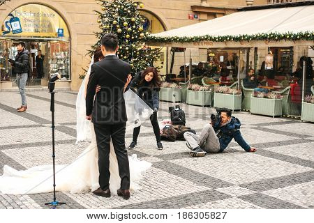 Prague, Czech Republic, December 24, 2016: The Asian photographer takes pictures of the wedding of a young beautiful Asian couple in Prague's main square. Wedding in Europe.