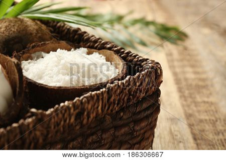 Wicker basket with desiccated coconut on wooden background