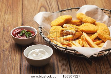 Chicken nuggets and french fries sauces of ketchup and mayonnaise on old wooden background.