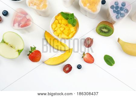 Bowls from automatic yogurt maker with fruits on white background