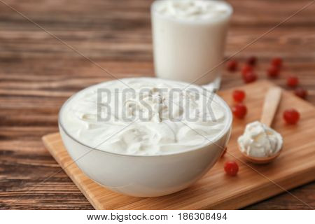 Bowl with yogurt on wooden board