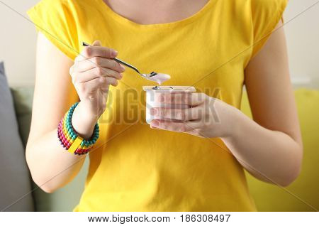 Woman holding plastic cup with yogurt and spoon, closeup