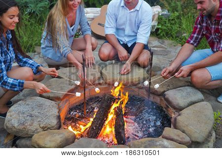 Company of young people holding sticks with marshmallows above campfire in the evening. Holiday and friendship concept