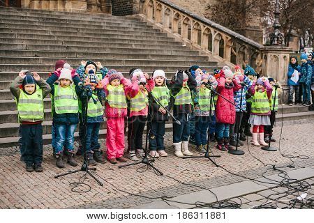 Prague, Czech Republic, December 15, 2016: The choir of children sing Christmas songs on the square next to the temple. People are watching the performance. Cozy Christmas celebrations.