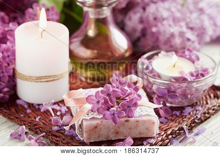 SPA concept: composition of spa treatment with natural sea salt aromatic oil and lilac flowers on white wooden background