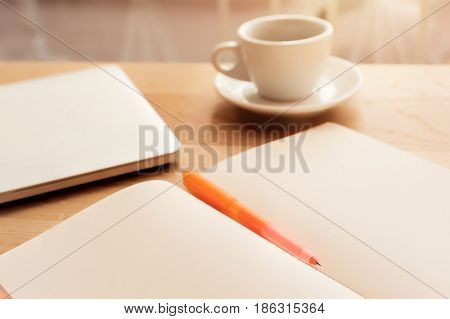Coffee Cup, Notebook And Pen On The Wooden Table