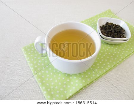 Cup of Ceylon silver white tea and loose tea leaves
