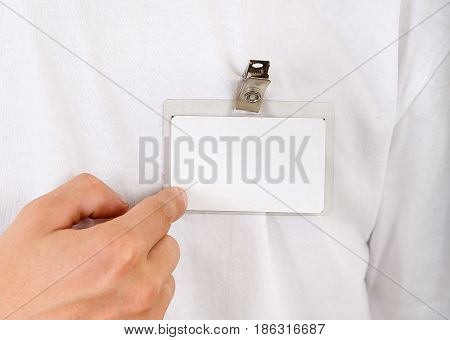 Person shows Blank Badge on the T-Shirt closeup