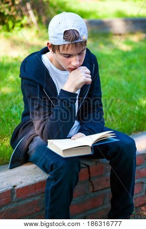 Teenager read a Books in the Summer Park