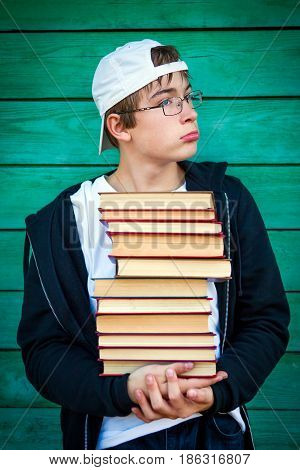 Sad Teenager with a Books by the Wooden Wall Background
