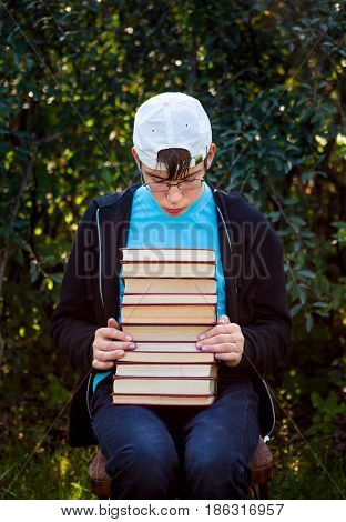 Sad Teenager with a Books sit on the Chair on the Nature Background